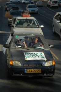 Hitorerut B'yerushalayim members symbolically driving cars filled with suitcases out of the city